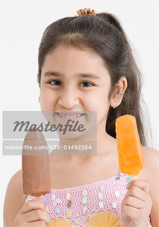 Portrait of a girl holding two ice creams Stock Photo - Premium Royalty-Free, Image code: 630-01492104