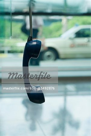 Close-up of a telephone receiver hanging Stock Photo - Premium Royalty-Free, Image code: 630-01492876