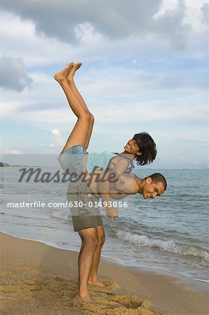 Side profile of a couple playing on the beach Stock Photo - Premium Royalty-Free, Image code: 630-01493056