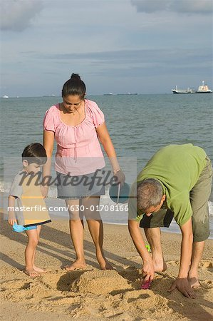 Mid adult couple making a sand castle on the beach with their son Stock Photo - Premium Royalty-Free, Image code: 630-01708166