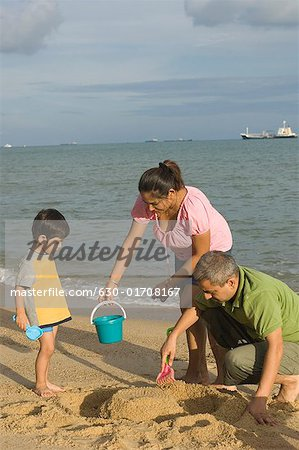 Mid adult couple making a sand castle on the beach with their son Stock Photo - Premium Royalty-Free, Image code: 630-01708167