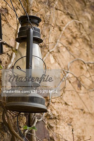 Close-up of a lantern hanging on a wall Stock Photo - Premium Royalty-Free, Image code: 630-01708406