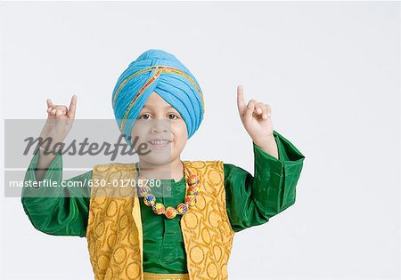 Portrait of a boy doing bhangra and smiling Stock Photo - Premium Royalty-Free, Image code: 630-01708780