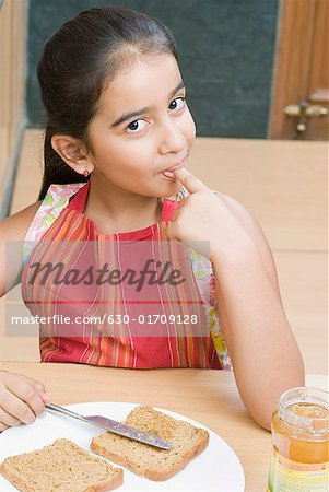 Portrait of a girl spreading jam on a bread slice and licking her finger