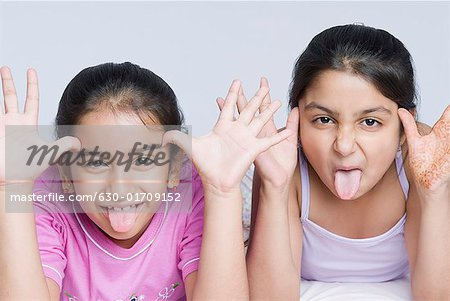 Portrait of two girls making their faces with sticking their tongues out Stock Photo - Premium Royalty-Free, Image code: 630-01709152
