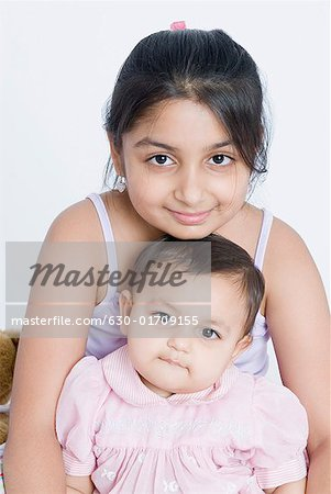 Portrait of a girl sitting with her sister Stock Photo - Premium Royalty-Free, Image code: 630-01709155
