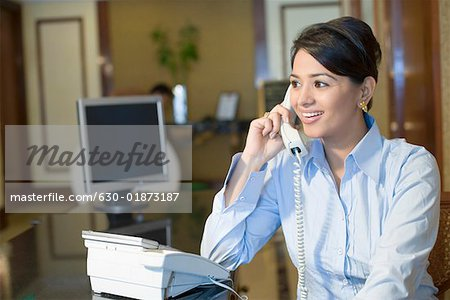 Close-up of a businesswoman talking on the telephone and smiling Stock Photo - Premium Royalty-Free, Image code: 630-01873187