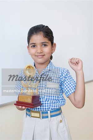 Portrait of a schoolgirl holding a trophy and smiling Stock Photo - Premium Royalty-Free, Image code: 630-01873517