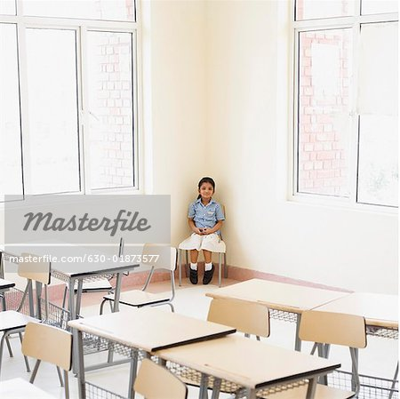 Schoolgirl sitting in the corner of a classroom Stock Photo - Premium Royalty-Free, Image code: 630-01873577