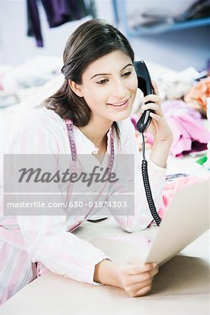 Close-up of a female fashion designer talking on the telephone Stock Photo - Premium Royalty-Free, Image code: 630-01874303