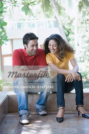 Young man sitting with a young woman and text messaging on a mobile phone Stock Photo - Premium Royalty-Free, Image code: 630-01875242