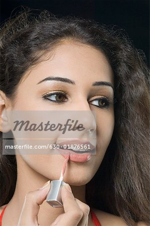 Close-up of a young woman applying lipstick Stock Photo - Premium Royalty-Free, Image code: 630-01876561