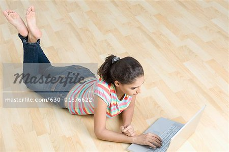 High angle view of a young woman lying on the floor and using a laptop Stock Photo - Premium Royalty-Free, Image code: 630-01876622
