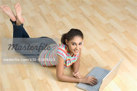 Portrait of a young woman lying on the floor and using a laptop Stock Photo - Premium Royalty-Free, Image code: 630-01876623