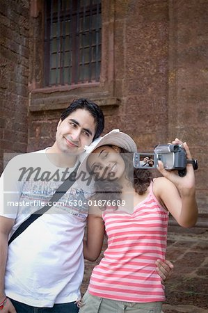 Young couple making a film of themselves with a home video camera, Goa, India