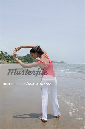 Rear view of a young woman exercising on the beach Stock Photo - Premium Royalty-Free, Image code: 630-01876782