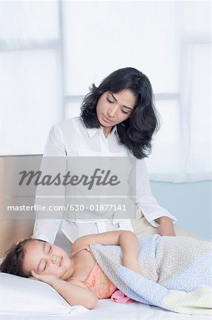 Girl sleeping on the bed with her mother sitting near her Stock Photo - Premium Royalty-Free, Image code: 630-01877141