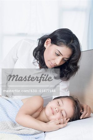 Young woman looking at her daughter sleeping on the bed Stock Photo - Premium Royalty-Free, Image code: 630-01877144