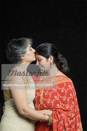 Side profile of a mature woman kissing on forehead of her daughter Stock Photo - Premium Royalty-Free, Image code: 630-01877600