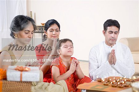 Family praying in front of figurines of God Stock Photo - Premium Royalty-Free, Image code: 630-01877607