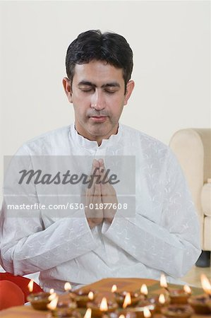 Close-up of a mid adult man praying with oil lamps in front of him Stock Photo - Premium Royalty-Free, Image code: 630-01877608