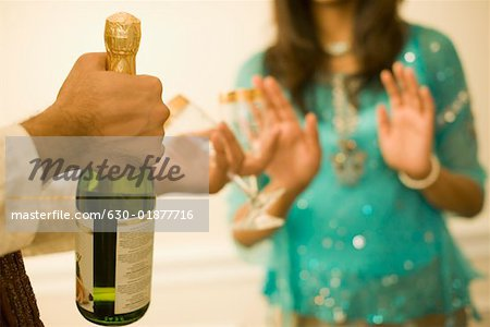 Close-up of a man's hand holding a champagne bottle Stock Photo - Premium Royalty-Free, Image code: 630-01877716