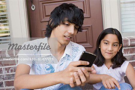 Teenage boy sitting with his sister Stock Photo - Premium Royalty-Free, Image code: 630-01877773