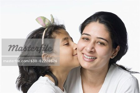 Close-up of a girl kissing her mother and smiling Stock Photo - Premium Royalty-Free, Image code: 630-02220526