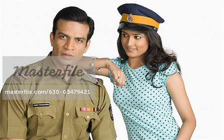 Portrait of a policeman with a young woman standing beside him Stock Photo - Premium Royalty-Free, Image code: 630-03479421