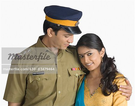 Police officer standing with his arm around his wife Stock Photo - Premium Royalty-Free, Image code: 630-03479464