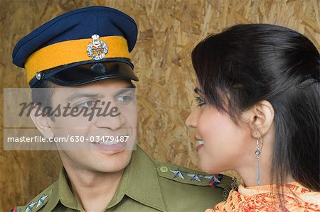 Close-up of a police man with his wife looking at each other and smiling Stock Photo - Premium Royalty-Free, Image code: 630-03479487