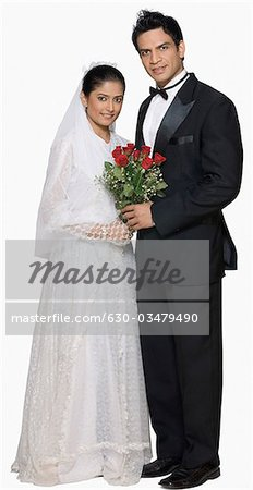 Portrait of a newlywed couple holding a bouquet of flowers and smiling Stock Photo - Premium Royalty-Free, Image code: 630-03479490