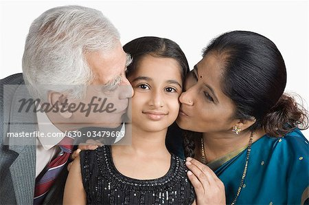 Senior man and a mature woman kissing their granddaughter Stock Photo - Premium Royalty-Free, Image code: 630-03479683