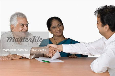 Couple discussing with a financial advisor Stock Photo - Premium Royalty-Free, Image code: 630-03479738