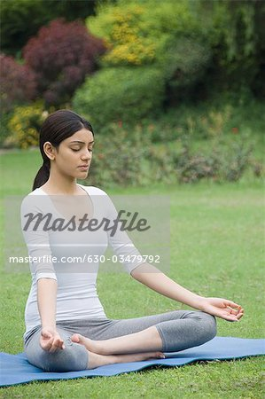 Woman practicing yoga in a park Stock Photo - Premium Royalty-Free, Image code: 630-03479792