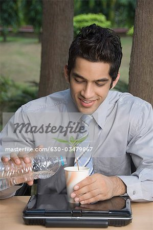 Businessman watering a plant Stock Photo - Premium Royalty-Free, Image code: 630-03479867