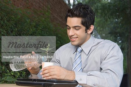 Businessman watering a plant Stock Photo - Premium Royalty-Free, Image code: 630-03479868