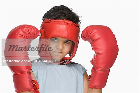 Portrait of a boy wearing boxing gloves and head protector Stock Photo - Premium Royalty-Free, Image code: 630-03481267