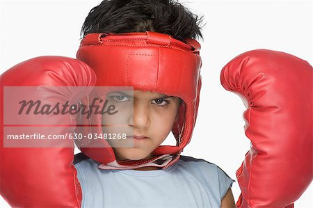 Portrait of a boy wearing boxing gloves and head protector Stock Photo - Premium Royalty-Free, Image code: 630-03481268