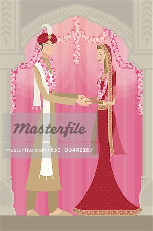 Indian bride and groom in traditional dress at wedding ceremony Stock Photo - Premium Royalty-Free, Image code: 630-03482187