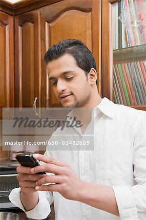 Man text messaging on a mobile phone Stock Photo - Premium Royalty-Free, Image code: 630-03482609