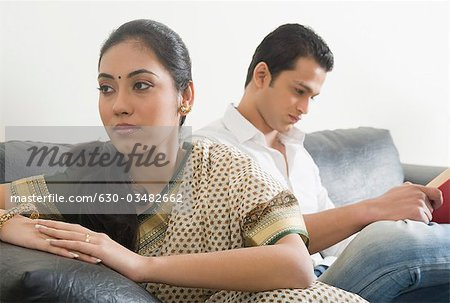 Woman looking sad with her husband reading a book Stock Photo - Premium Royalty-Free, Image code: 630-03482662