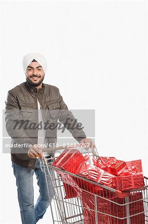 Portrait of a man pushing a shopping cart of gifts Stock Photo - Premium Royalty-Free, Image code: 630-03482757