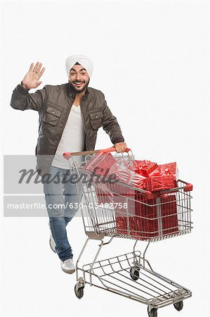 Man pushing a shopping cart of gifts Stock Photo - Premium Royalty-Free, Image code: 630-03482758