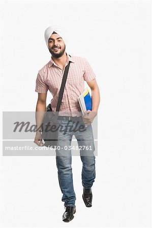University student holding a book and smiling Stock Photo - Premium Royalty-Free, Image code: 630-03482761