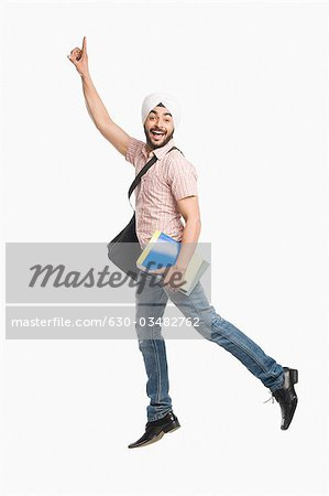 University student holding a book and smiling Stock Photo - Premium Royalty-Free, Image code: 630-03482762