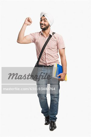 University student holding a book and smiling Stock Photo - Premium Royalty-Free, Image code: 630-03482764