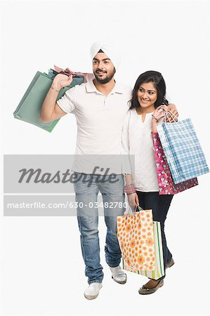 Couple carrying shopping bags and smiling Stock Photo - Premium Royalty-Free, Image code: 630-03482780