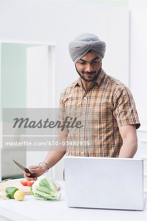 Man cooking with the recipe on a laptop Stock Photo - Premium Royalty-Free, Image code: 630-03482835