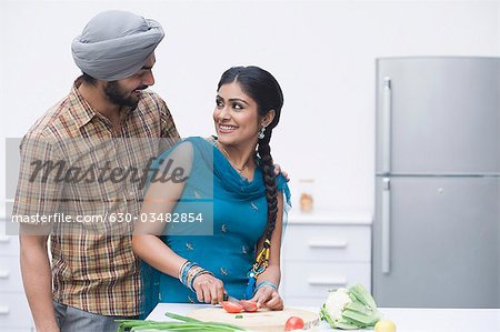 Couple chopping vegetables in the kitchen Stock Photo - Premium Royalty-Free, Image code: 630-03482854